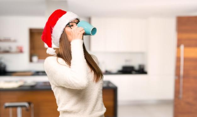 Ragazza con la celebrazione delle vacanze di natale che beve caffè caldo in tazza di carta da asporto a casa