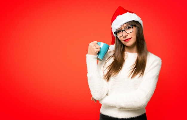 Ragazza con celebrando le vacanze di natale prendendo un caffè in tazza di carta da asporto