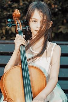 Una ragazza con un violoncello si siede nel parco su una panchina. musicista femminile. foto di alta qualità