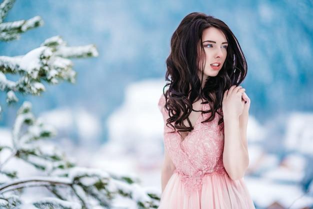 Ragazza con i capelli castani, gli occhi azzurri e un vestito rosa sullo sfondo delle montagne invernali