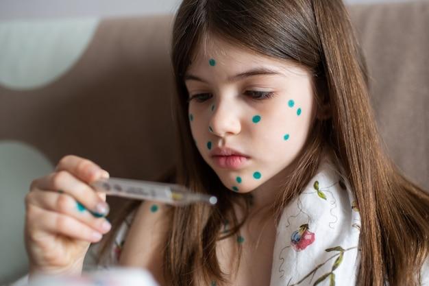 Una ragazza con la varicella misura la sua temperatura