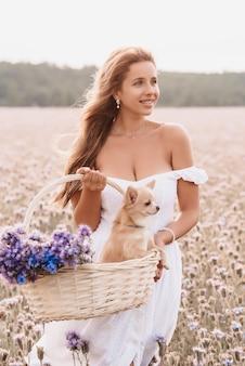 Ragazza con cane chihuahua in un cesto con un mazzo di fiori