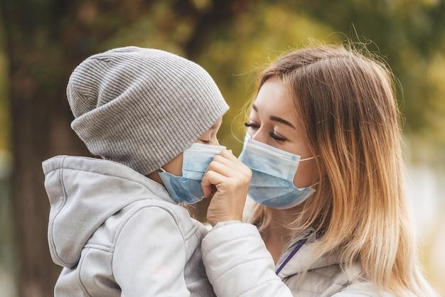 La ragazza con un bambino sta sulla strada in una mascherina medica protettiva in italia. coronovirus in europa