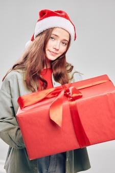 Ragazza con un regalo di natale in una scatola copricapo di sfondo grigio di capodanno