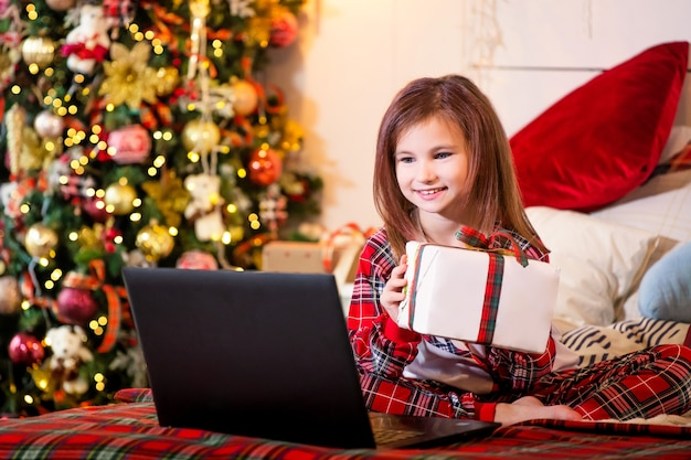 Una ragazza con un regalo di natale tra le mani si siede in pigiama sul letto davanti a un computer portatile sullo sfondo di un albero di natale.