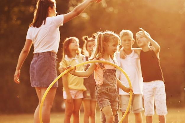 Ragazza con strumento di fitness cerchio. il gruppo di ragazzi ha un fine settimana attivo nel campo. illuminato da una bella luce solare.