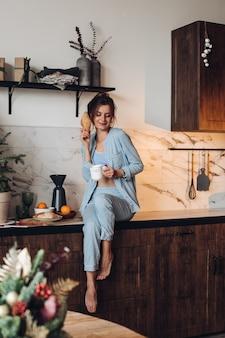 Ragazza con caffè e croissant in cucina.