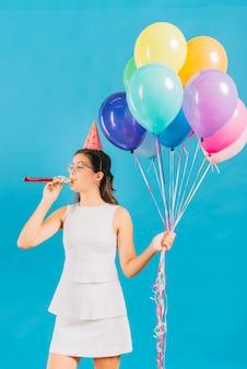 Ragazza con palloncini colorati che soffia corno di partito su sfondo blu
