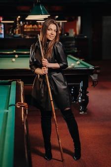 Una ragazza con una stecca in mano è in piedi in un club di biliardo. biliardo russo.
