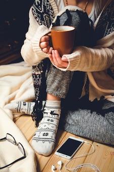 Ragazza con una tazza di caffè seduto su un pavimento di legno.