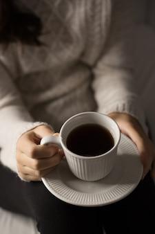 Ragazza con una tazza di tè, dettagli di mani