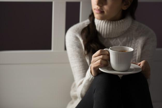 Ragazza con una tazza di tè seduto sul letto