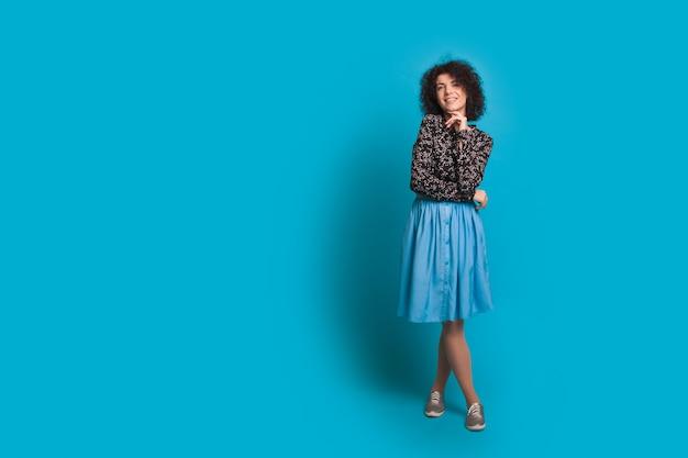 Ragazza con i capelli neri ricci è in posa in un vestito blu vicino allo spazio vuoto