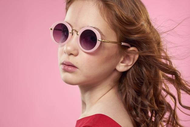 Ragazza con i capelli ricci scuri occhiali rotondi divertente sfondo rosso vestito rosa