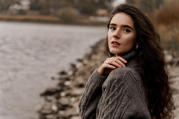 Ragazza con capelli ricci vicino al lago in autunno