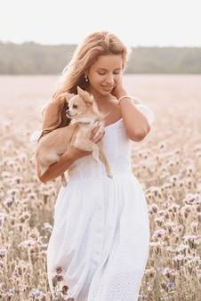 Ragazza con il simpatico cane a pelo lungo chihuahua all'aperto in estate nel campo