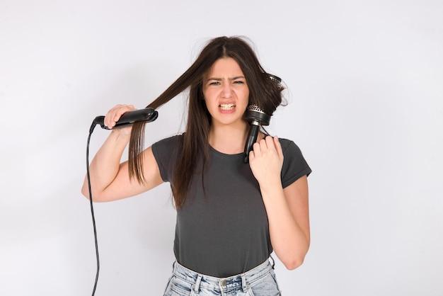 Ragazza con capelli danneggiati punte di capelli secchi infelici e fumo di ferro che brucia, concetto di capelli cattivi tagliati danneggiati