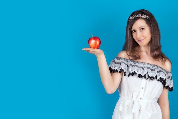 Ragazza con i capelli scuri spalle nude e collo che tiene una grande mela rossa