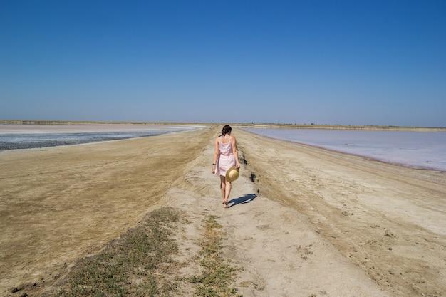 Una ragazza dai capelli scuri in un vestito e con un cappello di paglia che cammina a piedi nudi lungo le rive di un lago salato