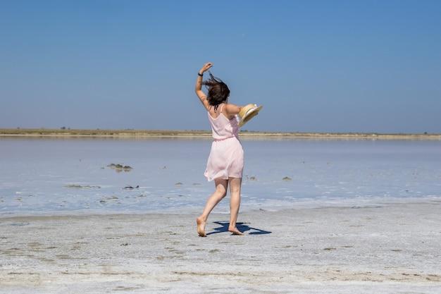 Una ragazza dai capelli scuri con un vestito rosa e un cappello di paglia corre a piedi nudi lungo le rive di un lago salato.