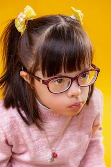 Ragazza con disordine. piccola signora dai capelli scuri risoluta che indossa una bella collana su un maglione rosa mentre pensa attivamente
