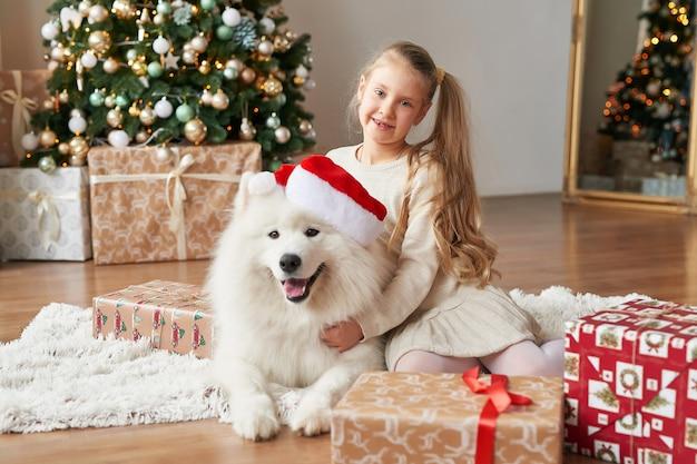 Ragazza con un cane vicino all'albero di natale sulla scena di natale