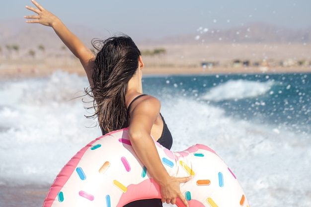Una ragazza con un cerchio di nuoto a forma di ciambella in riva al mare. il concetto di svago e intrattenimento in vacanza. Foto Premium