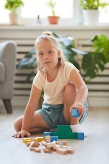 Ragazza con sindrome di down mentre gioca con i blocchi giocattolo sul pavimento a casa