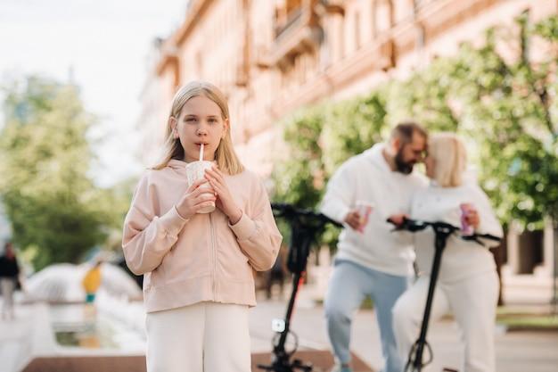 Una ragazza con un drink in mano è in piedi in città e dietro di lei su scooter elettrici ci sono i suoi genitori.