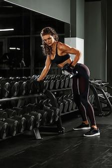 Una ragazza con manubri è impegnata nel bodybuilding sullo sfondo della palestra, una donna è impegnata nel fitness con manubri nella sala fitness.