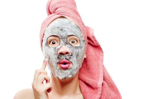 Ragazza con maschera facciale, maschera di ossigeno per il viso, ragazza felice si prende cura della pelle del viso, ritratto ravvicinato di una ragazza con un asciugamano rosa sulla testa su uno sfondo bianco isolato, sorpresa