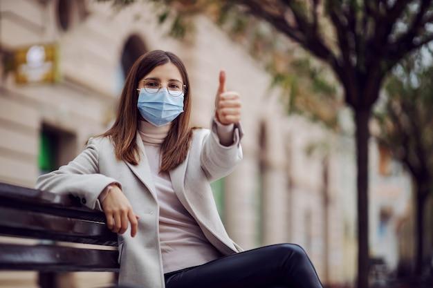 Ragazza con la maschera per il viso sulla seduta su una panchina fuori durante il virus corona