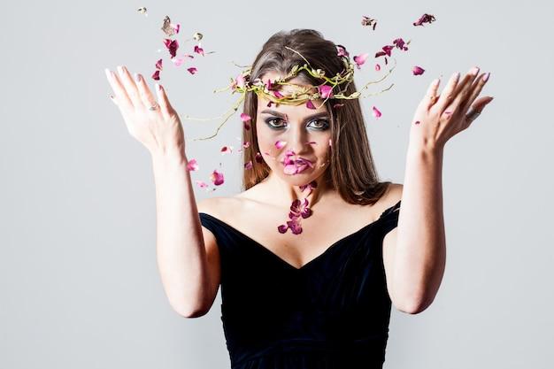 La ragazza con il trucco alla moda ha sparso i petali di rose secchi