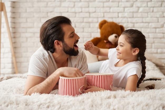 Ragazza con padre guarda commedia e mangia popcorn.
