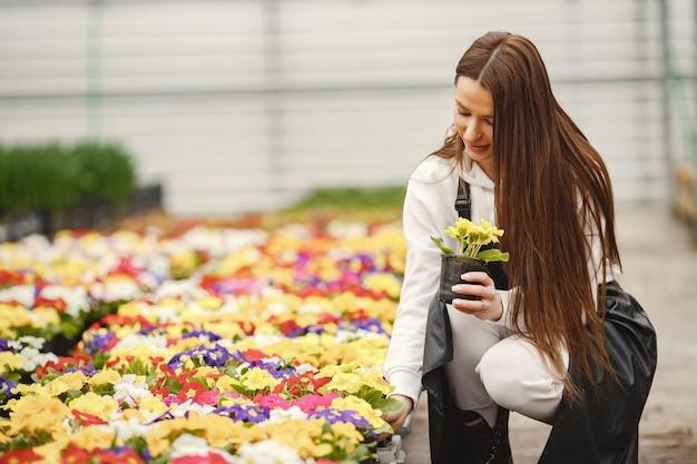 Ragazza con fiori in una serra. giardiniere in un grembiule. cura dei fiori.