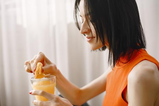 Ragazza con un bicchiere di succo di frutta seduto sul pavimento.