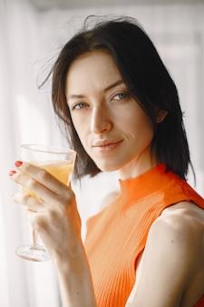 Ragazza con un bicchiere di succo in piedi vicino alla finestra.