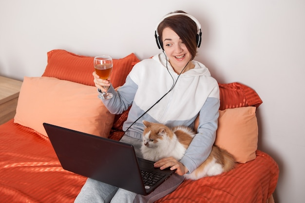 Una ragazza con un bicchiere di vino comunica online con amici e parenti.