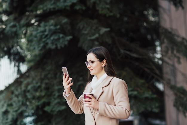 Ragazza con gli occhiali e la tazza di caffè utilizza un telefono