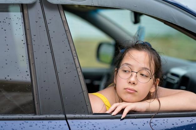 Ragazza con gli occhiali che guarda fuori dal finestrino dell'auto concetto di viaggio su strada