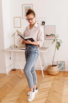 Ragazza con gli occhiali che legge un libro vicino al desktop a casa