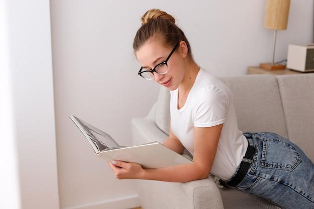 La ragazza con gli occhiali legge la rivista sdraiata sul divano