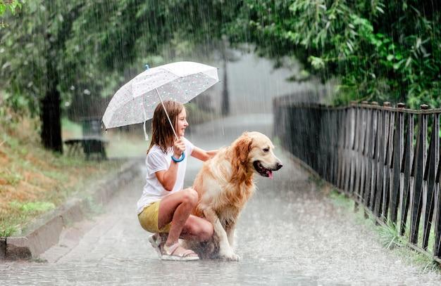 Ragazza con cane golden retriever in una giornata di pioggia Foto Premium