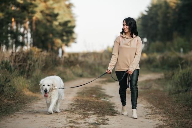 Ragazza con il cane golden retriever che cammina sulla strada forestale