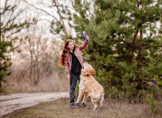 Ragazza con cane golden retriever nel bosco