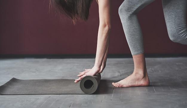 La ragazza con un buon tipo di corpo fitness ha esercizi nella stanza spaziosa