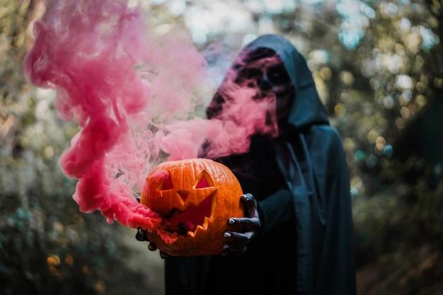 Ragazza con costume di halloween e trucco, che tiene una zucca con una bomba fumogena all'interno