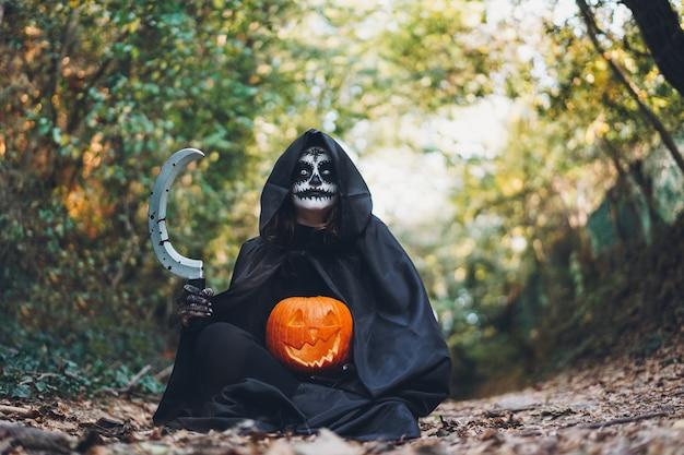 Ragazza con trucco di halloween, che tiene una falce con il sangue e una zucca nel legno