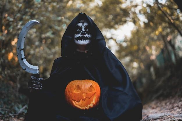 Ragazza con trucco di halloween, che tiene una falce con il sangue e una zucca nel bosco