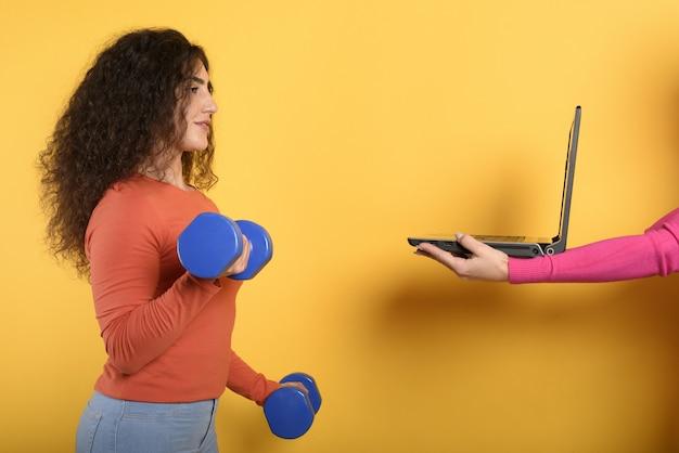 Ragazza con manubri pronta per iniziare la palestra online con un computer. muro giallo